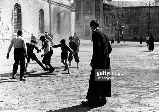 A vicar referees a game of football played outside a city church