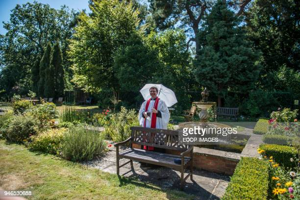 A vicar standing with an umbrella in a rose garden