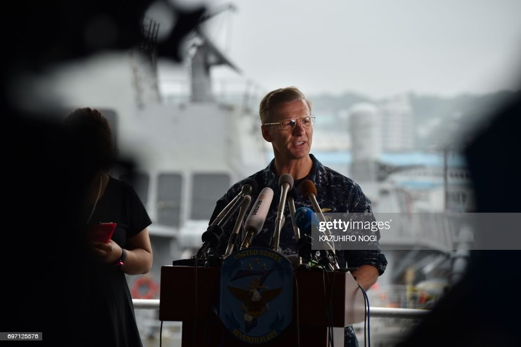 Vice Adm. Joseph Aucoin, Commander of the US 7th Fleet, delivers a speech during a press conference in front of the guided missile destroyer USS Fitzgerald at US Navy Yokosuka Base, southwest of Tokyo on June 18, 2017. A number of missing American sailors have been found dead in flooded areas of a destroyer that collided with a container ship off Japan's coast, the US Navy said on June 18, 2017. / AFP PHOTO / Kazuhiro NOGI
