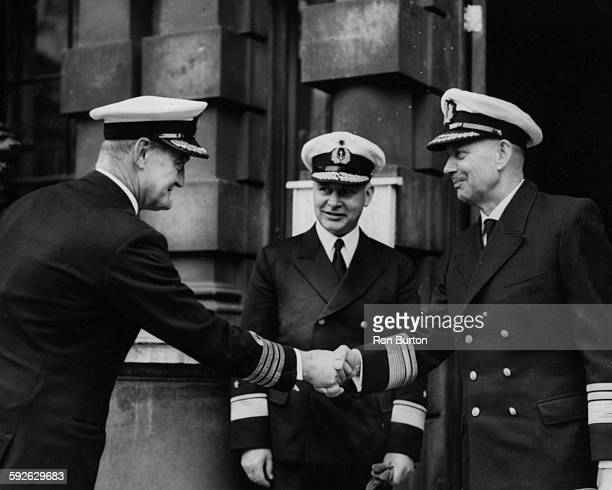 Vice Admiral Friedrich Ruge Inspector General of the West German Navy is greeted by Captain P Howes the First Sea Lord's Naval Assistant watched by...