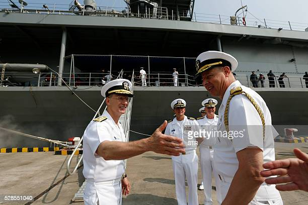Vice Admiral Joseph P Aucoin Commander of the US Seventh Fleet is greeted as he disembarks from the USS Blue Ridge in Shanghai on May 6 2016 China...