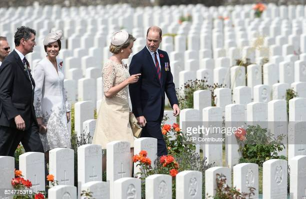 Vice Admiral Sir Timothy Laurence and Catherine Duchess of Cambridge and Queen Mathilde of Belgium and Britain's Prince William walk past headstones...