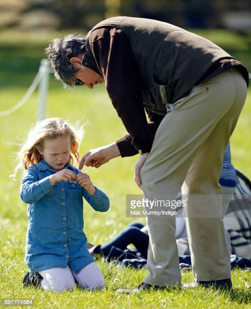 Vice Admiral Sir Timothy Laurence helps Savannah Phillips make a daisy chain as they attend the Gatcombe Horse Trials at Gatcombe Park on March 25...
