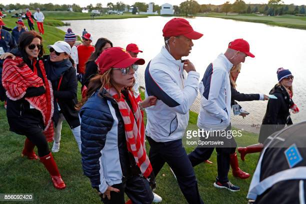 USA vice captain Tiger Woods walks the 18th hole with Erica Herman during the third round of the Presidents Cup at Liberty National Golf Club on...