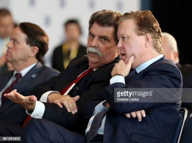 Vice Chairman of NASCAR Mike Helton speaks to NASCAR Chief Executive Officer and Chairman Brian France during the NACAR Hall of Fame Voting Day at...