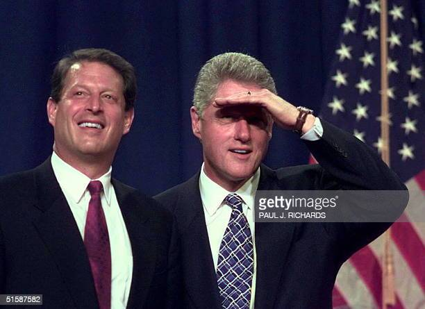 Vice President Al Gore and US President Bill Clinton look through the lights and into the crowd gathered to hear their speech 27 October at...