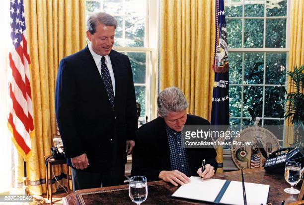 Vice President Al Gore watches as US President Bill Clinton signs an Executive Order in the White House's Oval Office, Washington DC, August 9, 1997....