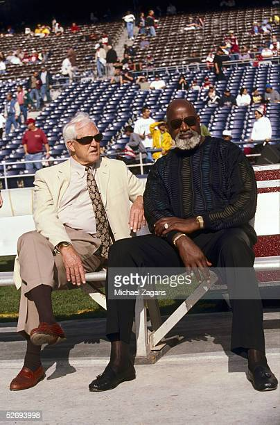 Vice President and General Manager Bill Walsh of the San Francisco 49ers meets with team consultant Harry Edwards prior to their game against the San...