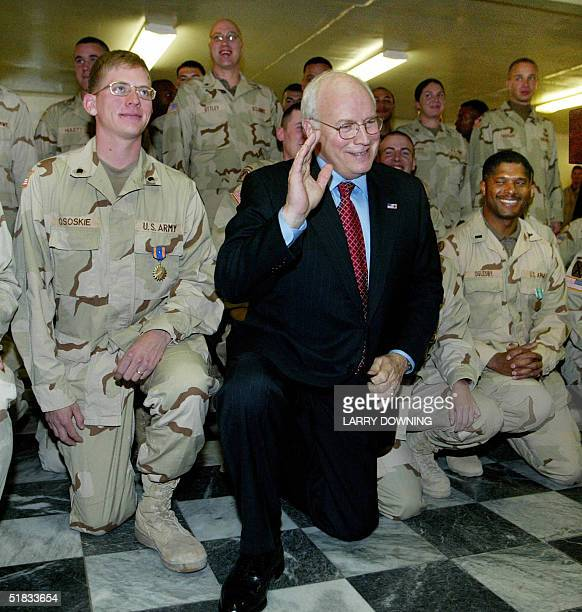 Vice President Dick Cheney gets on his knee during a photo session with soldiers from the 25th Infantry Division following a US military medal...