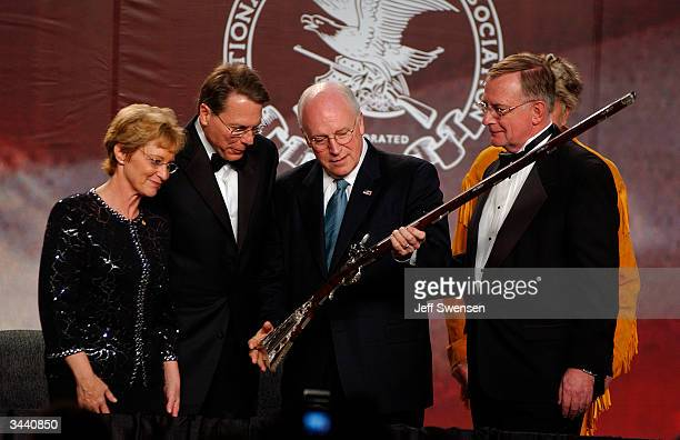 Vice President Dick Cheney inspects a flintlock rifle given to him by the National Rifle Association while he is surrounded by NRA officers Sandra...
