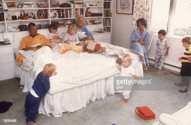 Vice president George Bush and his wife Barbara relax in bed as their daughter and grandchildren join them at home in Kennebunkport, Maine, 1987.