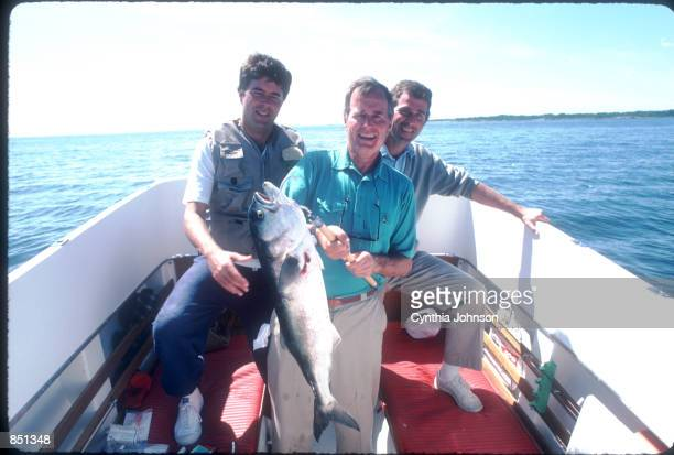 Vice President George Bush sits with his sons George W and Jeb while holding a fish August 1983 in Kennebunkport ME Bush is vacationing in Maine with...