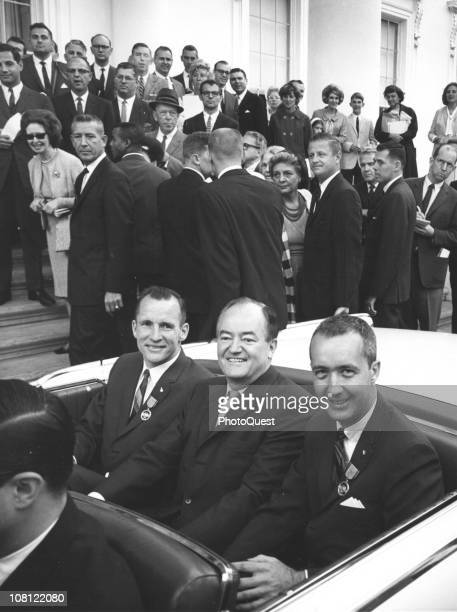 US Vice President Hubert Humphrey sits between American astronauts Ed White and James A McDivitt in a convertible outside the White House Washington...