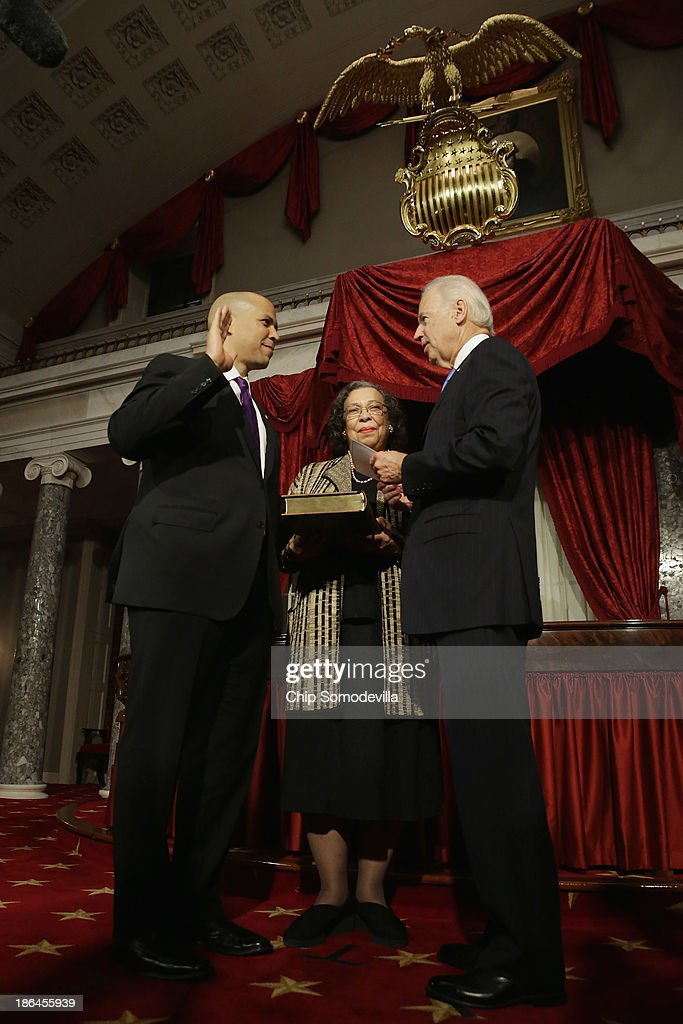 U.S. Vice President Joe Biden (R) administers a ceremonial swearing for Sen. Cory Booker (D-NJ) (L) as his mother Carolyn Booker holds a Bible in the Old Senate Chamber at the U.S. Capitol October 31, 2013 in Washington, DC. Booker defeated Republican Steve Lonegan in a special election to replace Frank Lautenberg, who died in June.