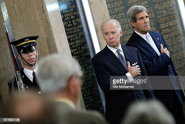 S Vice President Joe Biden and US Secretary of State John Kerry place their hands over their hearts during the presentation of the American flag at a...
