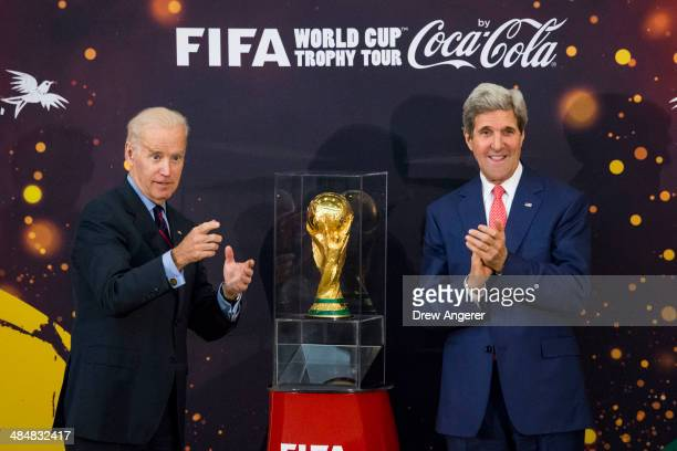 S Vice President Joe Biden and US Secretary of State John Kerry unveil the World Cup trophy during a FIFA World Cup Trophy Tour event at the US State...