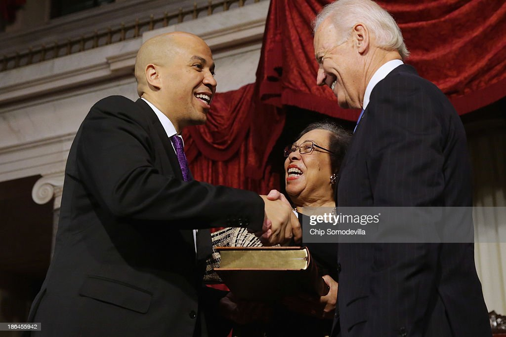 U.S. Vice President Joe Biden (R) congratulates Sen. Cory Booker (D-NJ) (L) after administering a ceremonial swearing-in as his mother Carolyn Booker looks on in the Old Senate Chamber at the U.S. Capitol October 31, 2013 in Washington, DC. Booker defeated Republican Steve Lonegan in a special election to replace Frank Lautenberg, who died in June.