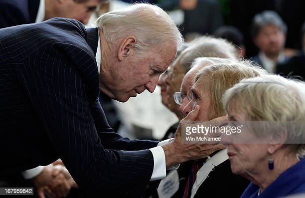 S Vice President Joe Biden embraces family members of American Foreign Service Association members who died while serving overseas during a ceremony...