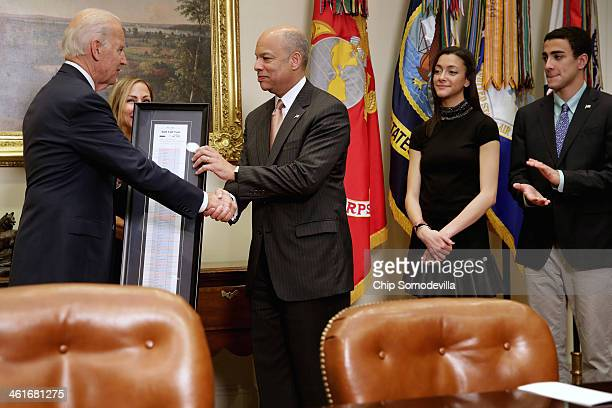 US Vice President Joe Biden gives Homeland Security Secretary Jeh Johnson the framed roll call tally sheet of his confirmation vote after ceremonally...