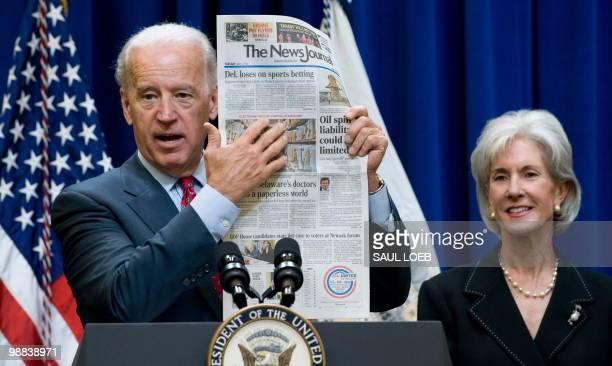 US Vice President Joe Biden holds up a copy of the Wilimington News Journal alongside Secretary of Health and Human Services Kathleen Sebelius to...