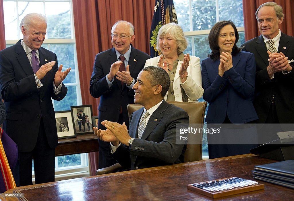 U.S. Vice President Joe Biden (L), Interior Secretary Ken Salazar (2nd-L) and others react after U.S. President Barack Obama signed a bill designating the First State Monument, in Delaware, a National Monument, during a bill signing ceremony in the Oval Office at the White House on March 25, 2013 in Washington, D.C. President Obama signed a series of bills designating five new National Monuments, including, Rio Grande del Norte in New Mexico, the First State Monument in Delaware, the Harriet Tubman Underground Railroad in Maryland, the Charles Young Buffalo Soldiers in Ohio and the San Juan Islands in Washington.