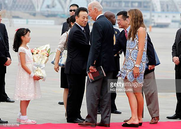 US Vice President Joe Biden is presented with flowers as he his granddaughter Naomi Biden and US ambassador to China Gary Locke arrive on Air Force...
