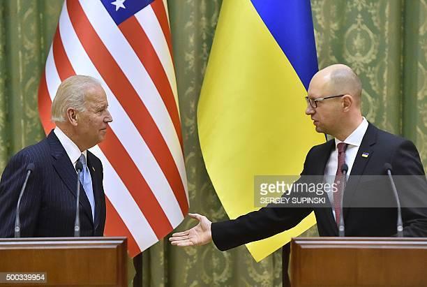 US Vice President Joe Biden listens as Ukrainian Prime Minister Arseniy Yatsenyuk delivers a statement on the results of talks in Kiev on December 7...