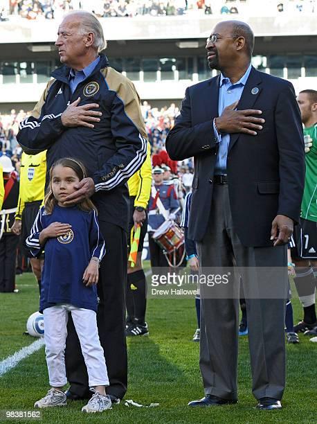 Vice President Joe Biden Mayor Michael Nutter of Philadelphia and Biden's granddaughter Natalie Biden observe the National Anthem before the game...