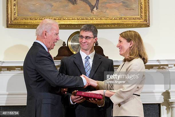 Vice President Joe Biden shakes hands with new Health and Human Services Secretary Sylvia Burwell while her husband Stephen Burwell looks on during a...