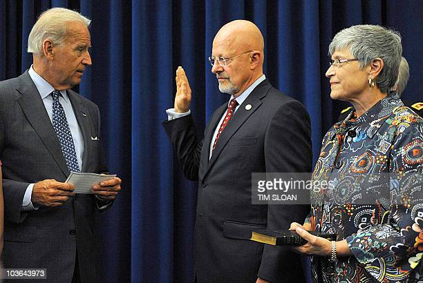 US Vice President Joe Biden swears in Director of National Intelligence James Clapper while his wife Sue Clapper holds a bible on August 24 2010 at...