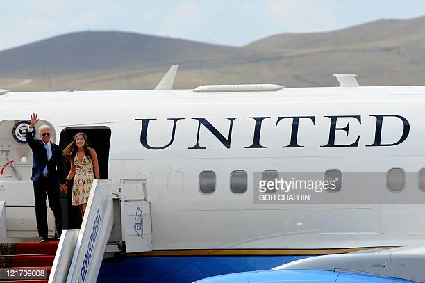 US Vice President Joe Biden waves as he and his granddaughter Naomi Biden exit from Air Force Two upon arrival at the Chinggis Khaan International...