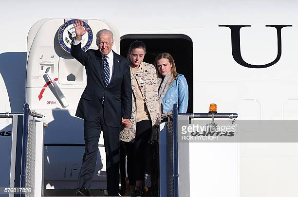 US Vice President Joe Biden waves as he arrives in Sydney with his granddaughters Naomi and Finnegan on July 18 2016 Biden who is touring Australia...