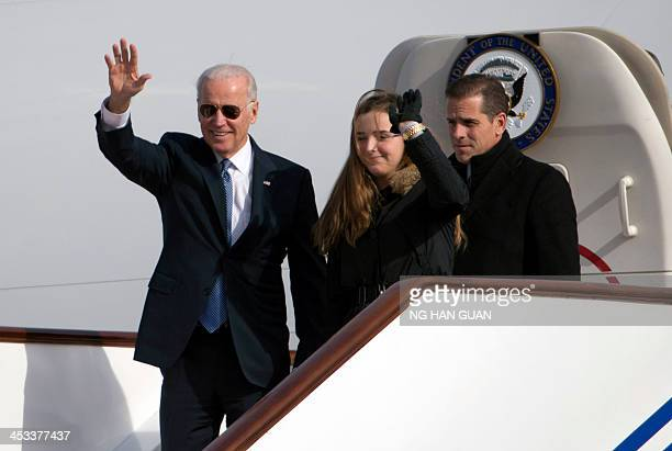 US Vice President Joe Biden waves as he walks out of Air Force Two with his granddaughter Finnegan Biden and son Hunter Biden upon their arrival in...
