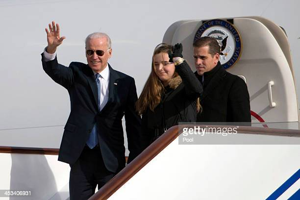 S Vice President Joe Biden waves as he walks out of Air Force Two with his granddaughter Finnegan Biden and son Hunter Biden on December 4 2013 in...
