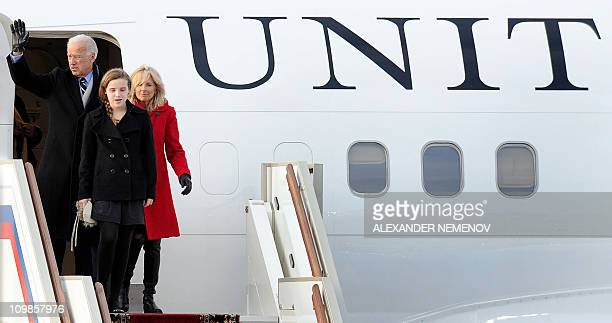 US Vice President Joe Biden waves standing next to his wife Jill and granddaughter Finnegan just after landing at Vnukovo International Airport...