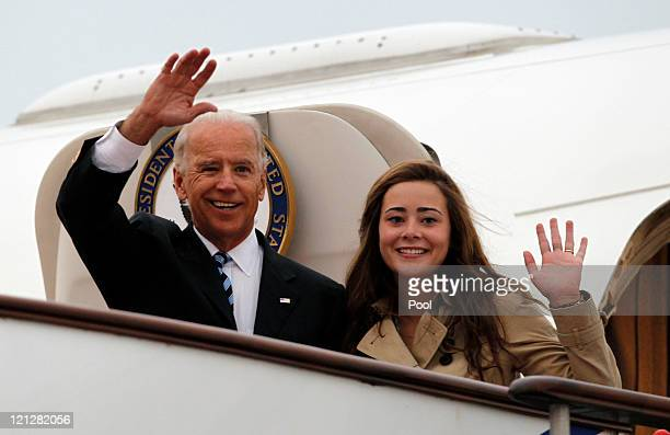 S Vice President Joe Biden waves with his granddaughter Naomi Biden as they walk out from Air Force Two upon arrival at the Beijing Capital...
