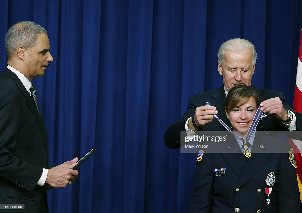 U.S. Vice President Joseph Biden (R) and Attorney General Eric Holder (L) give the Medal of Valor to Firefighter Hope Scott, of the Virginia Beach Fire Department, during an event in Eisenhower Executive Office Building, February 20, 2013 in Washington, DC. Vice President Biden presented the award to public safety officers who have exhibited exceptional courage, regardless of personal safety, in the attempt to save or protect others from harm.
