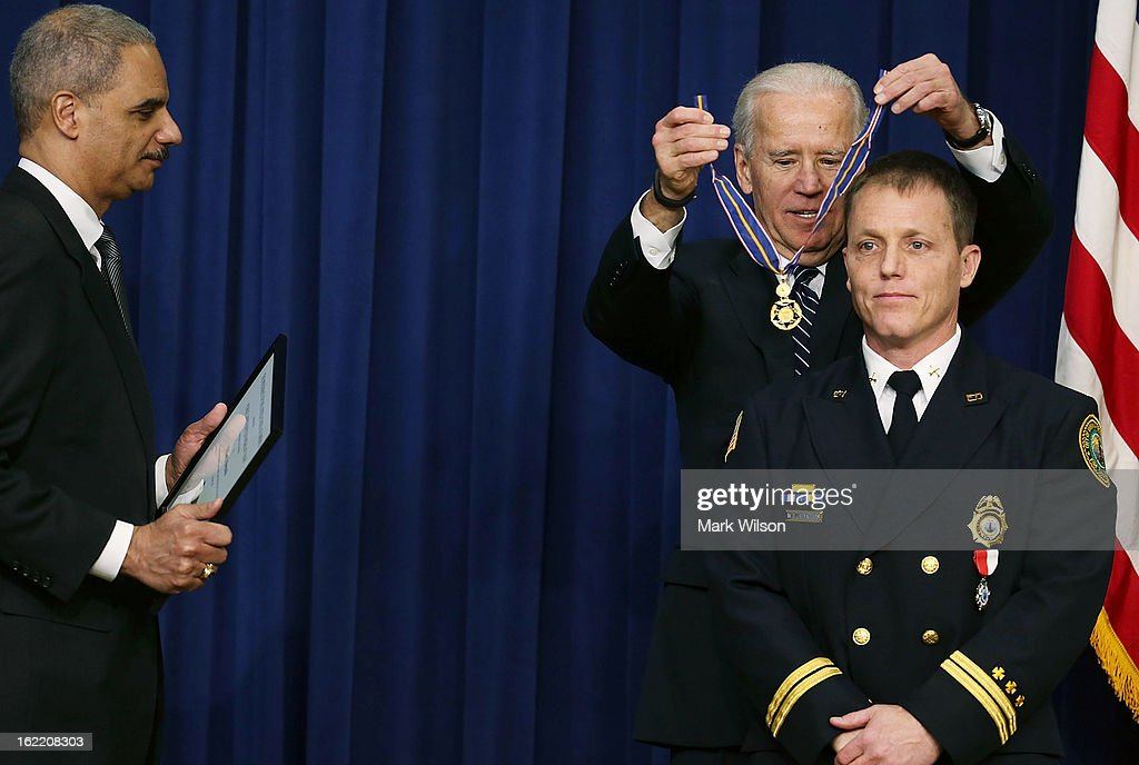 U.S. Vice President Joseph Biden (R) and Attorney General Eric Holder (L) give the Medal of Valor to Battalion Chief William Reynolds, of the Virginia Beach Fire Department, during an event in Eisenhower Executive Office Building, February 20, 2013 in Washington, DC. Vice President Biden presented the award to public safety officers who have exhibited exceptional courage, regardless of personal safety, in the attempt to save or protect others from harm.