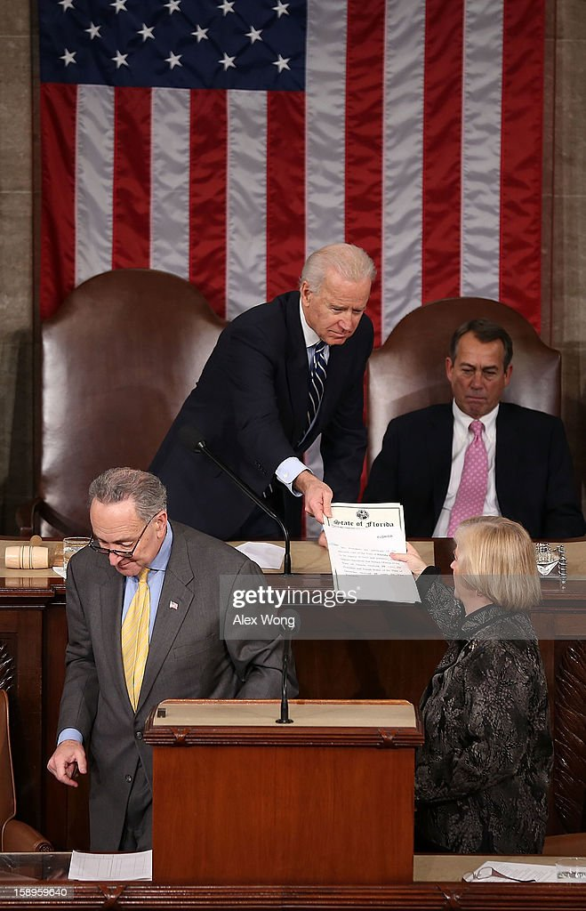 U.S. Vice President Joseph Biden (L) hands a vote certificate to Rep. Candice Miller, lower right, as Speaker of the House Rep. John Boehner (R-OH), upper right, looks on during a joint session of the 113th Congress to count the Electoral College votes January 4, 2013 on Capitol Hill in Washington, DC. The Senate and the House held a joint session to count the Electoral College votes for the 2012 presidential election.
