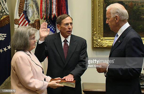 Vice President Joseph Biden swears in David Petraeus to be Director of the Central Intelligence Agency while his wife Holly Petraeus holds a Bible in...