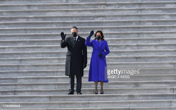 Vice President Kamala Harris and her husband US Second Gentleman Doug Emhoff wave as former US Vice President Mike Pence departs after the...