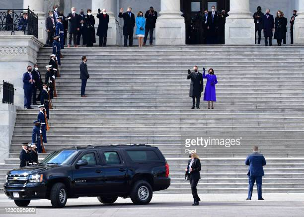 Vice President Kamala Harris and husband Douglas Emhoff wave on the east side steps of the U.S. Capitol as former U.S. Vice President Mike Pence and...