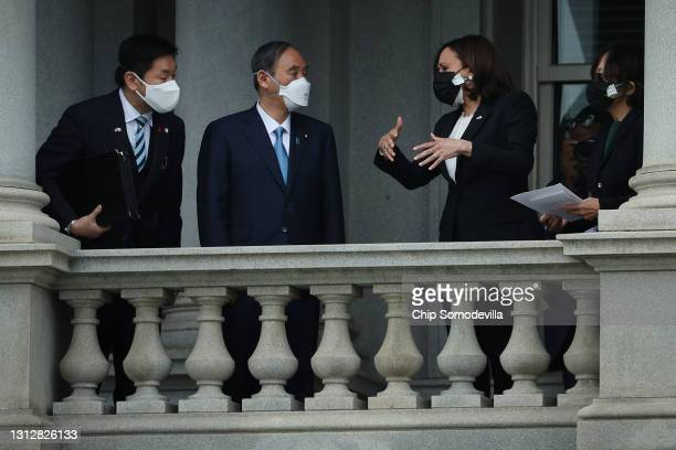 Vice President Kamala Harris and Japanese Prime Minister Yoshihide Suga look at the White House from a balcony of the Eisenhower Executive Office...