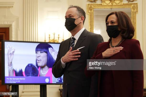 Vice President Kamala Harris and Second Gentleman Doug Emhoff listen to the national anthem as they watch the virtual presidential inaugural prayer...