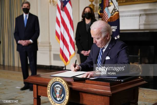 Vice President Kamala Harris and Special Presidential Envoy for Climate John Kerry watch as US President Joe Biden signs executive orders after...