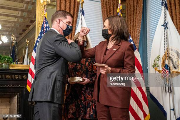 Vice President Kamala Harris elbow bumps Marty Walsh, U.S. Secretary of labor, during a swearing in ceremony in the Eisenhower Executive Office...