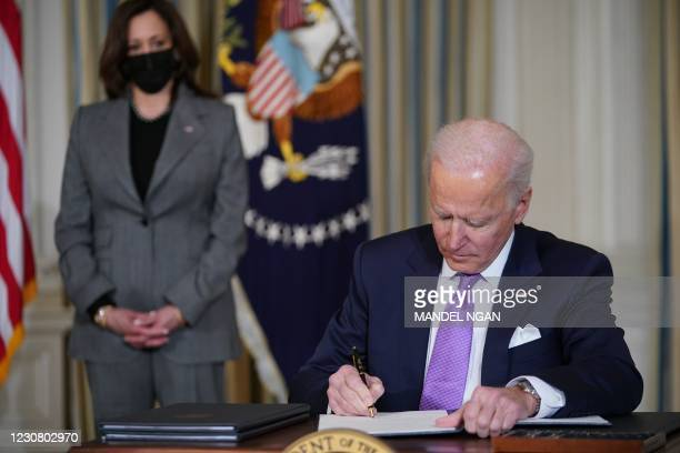 Vice President Kamala Harris watches as US President Joe Biden signs executive orders after speaking on racial equity in the State Dining Room of the...