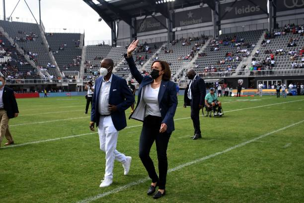 Vice President Kamala Harris, with Howard University President Wayne A. I. Frederick , waves as she leaves the field after tossing the coin for the...