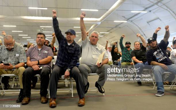 ILWU vice president local 13 Gary Herrera and president Ray Familathe raise their fists along with other members during the Harbor Commission meeting...