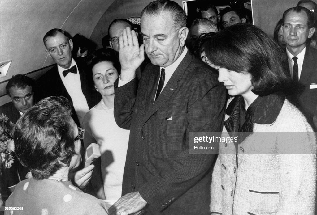 Vice President Lyndon B. Johnson is sworn in to the office of the Presidency aboard Air Force One in Dallas, Texas, hours after the assassination of President John F. Kennedy. Johnson is flanked by wife, Lady Bird Johnson (L), and First Lady Jacqueline Kennedy during the ceremony, which is being administered by U.S. District Judge Sarah Hughes. At farthest left in the background is Jack Valenti.